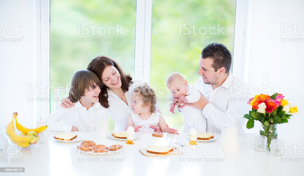 Young family with three children enjoying breakfast near big window stock photo