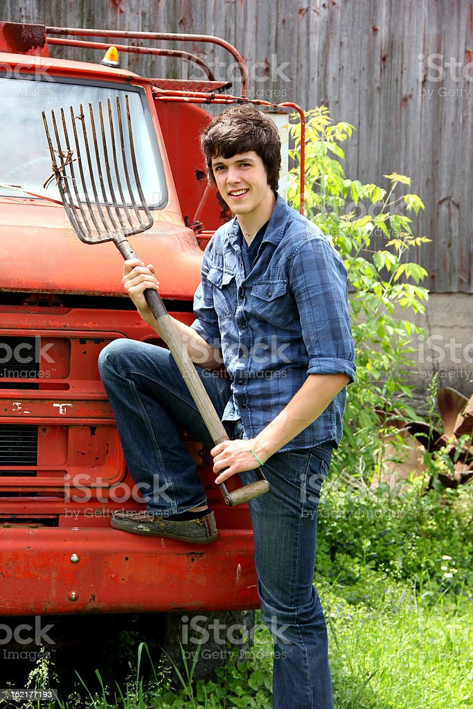 Young Farm Boy with Rake and Truck royalty-free stock photo