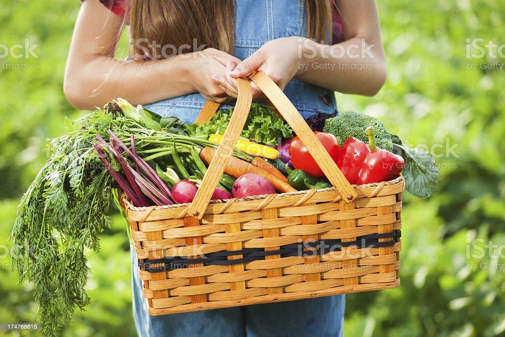 Young Farm Girl Holding Basket of Freshly Harvested Produce royalty-free stock photo
