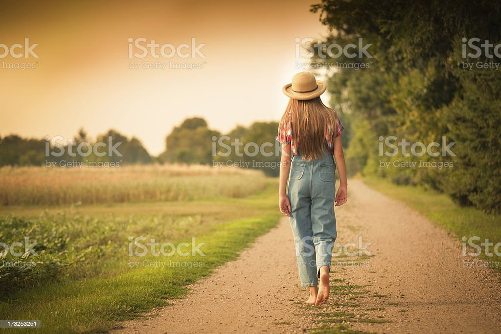 Young Farm Girl Walking in Country Road by the Field royalty-free stock photo