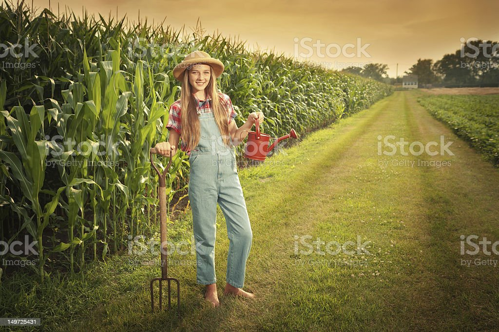 Young Farmer Girl Holding Gardening Tools by the Field Hz stock photo