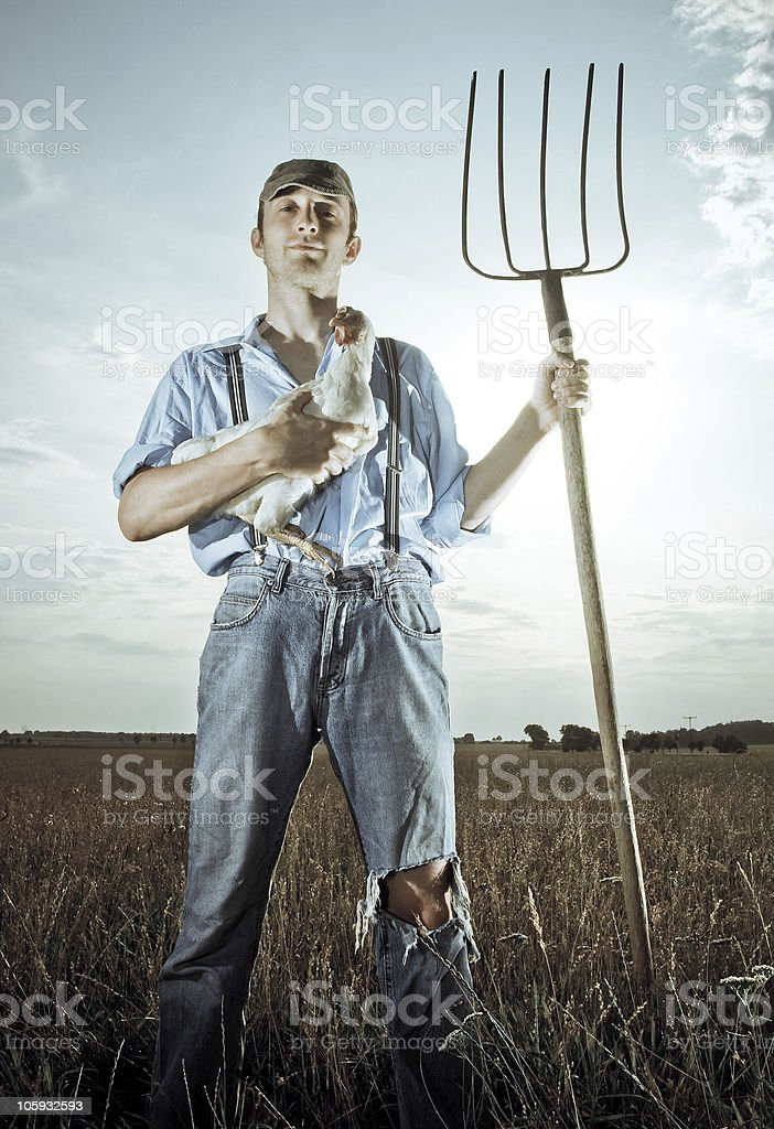 A young farmer holding a chicken and pitchfork stock photo