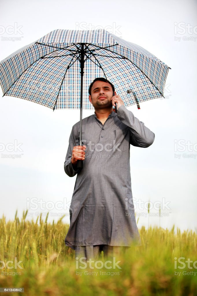 Young farmer standing in green field and talking on mobile phone stock photo