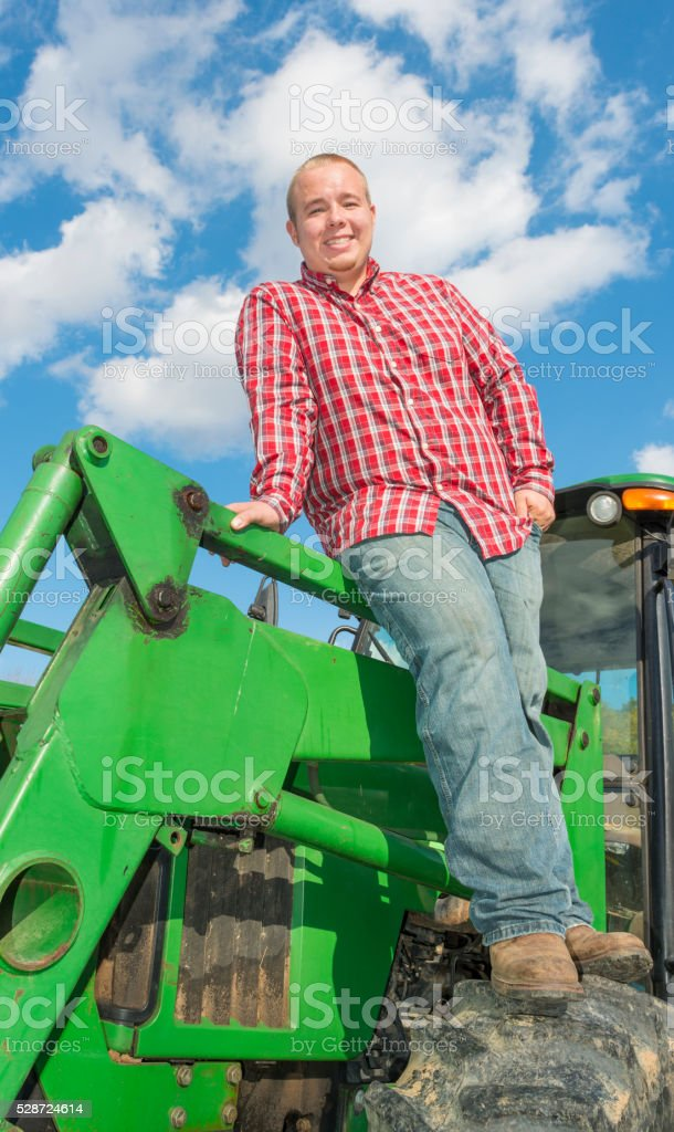 Young Farmer standing on tractor tire stock photo
