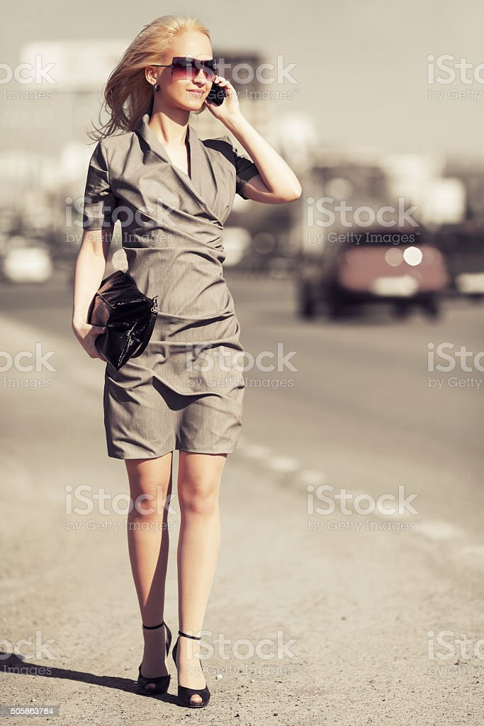 Young fashion blond woman calling on cell phone outdoor stock photo