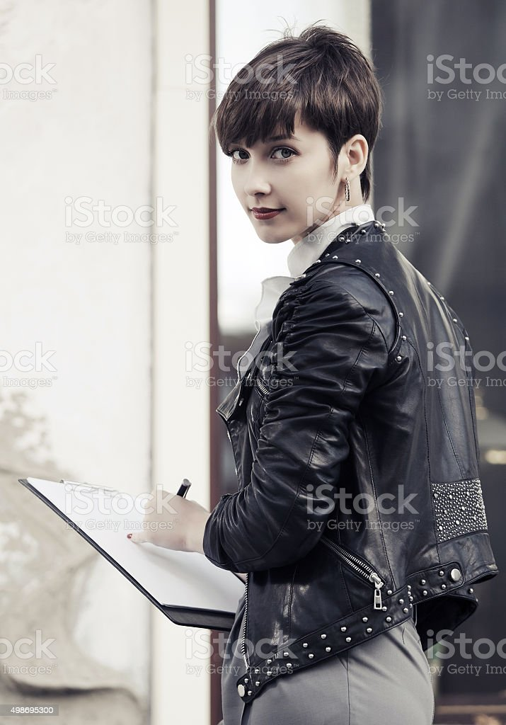 Young fashion business woman in leather jacket with clipboard stock photo