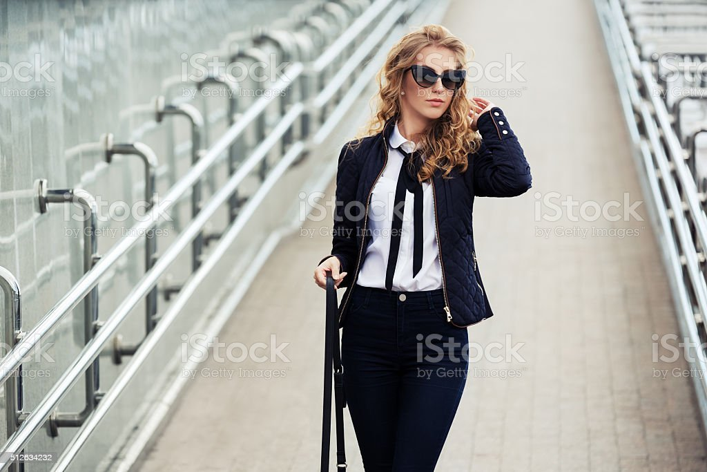 Young fashion business woman walking on the city street stock photo