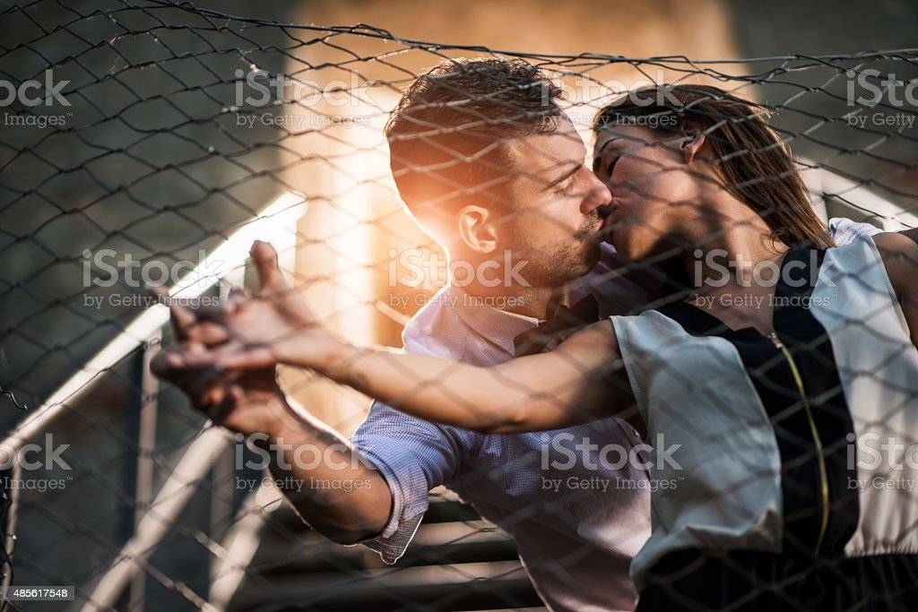 Young fashion couple kissing each other outdoors. stock photo