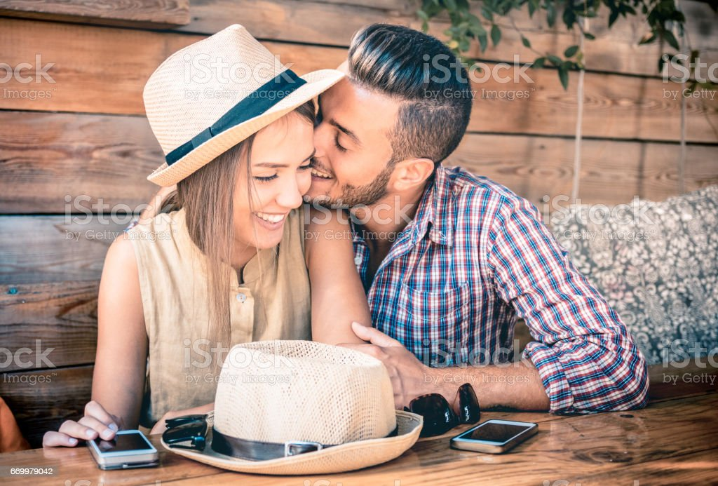 Young fashion couple of lovers at beginning of love story - Handsome man whispers sexy kisses in pretty woman ear - Relationship love concept with boyfriend and girlfriend together - Warm retro filter stock photo