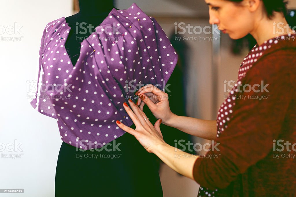 Young fashion designer is working in her workshop stock photo