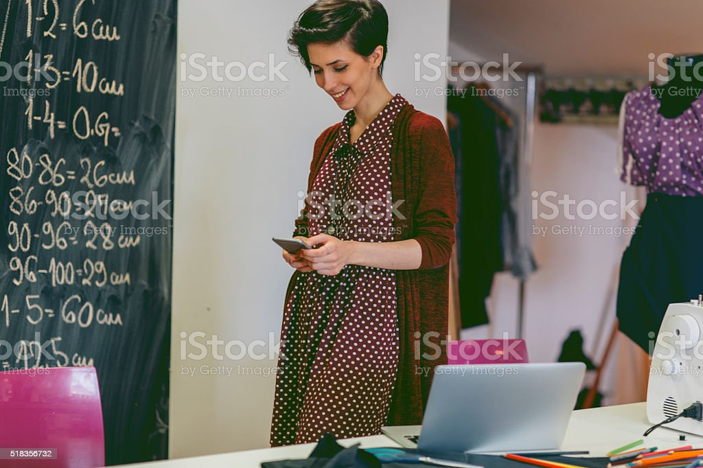 Young fashion designer using smart phone in her workshop stock photo