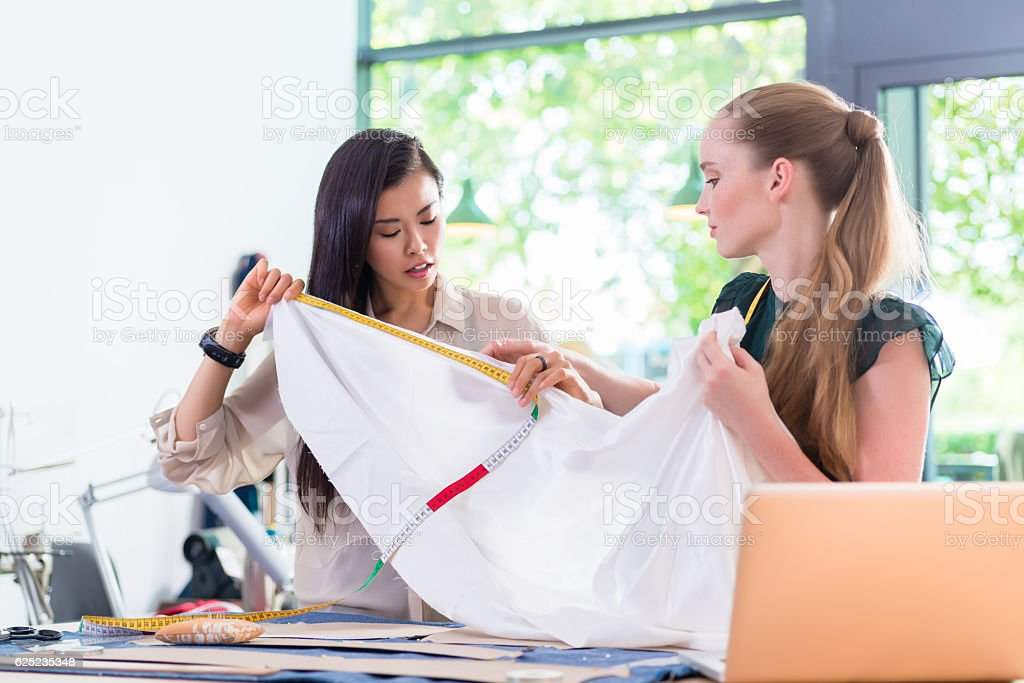 Young Fashion designer women measuring cloth stock photo