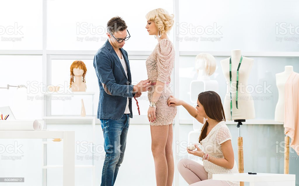 Young fashion designers with customer in design studio. stock photo