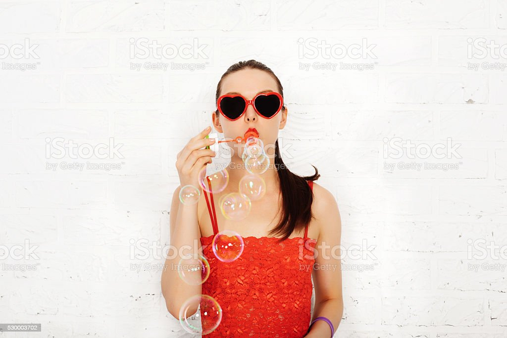 Young Fashion Girl in red sunglasses blowing bubbles stock photo