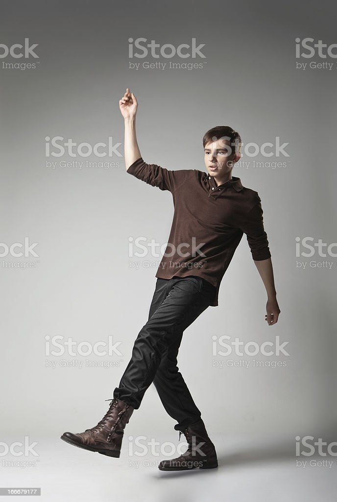 Young fashion male jumping on grey background royalty-free stock photo