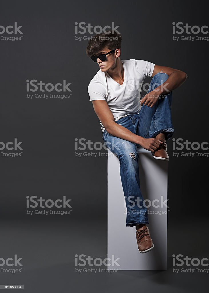 Young fashion man sitting on white rectangle royalty-free stock photo
