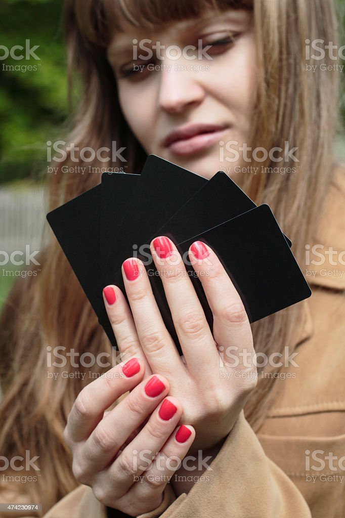 Red nails against black playing cards Latvian girl outdoors stock photo