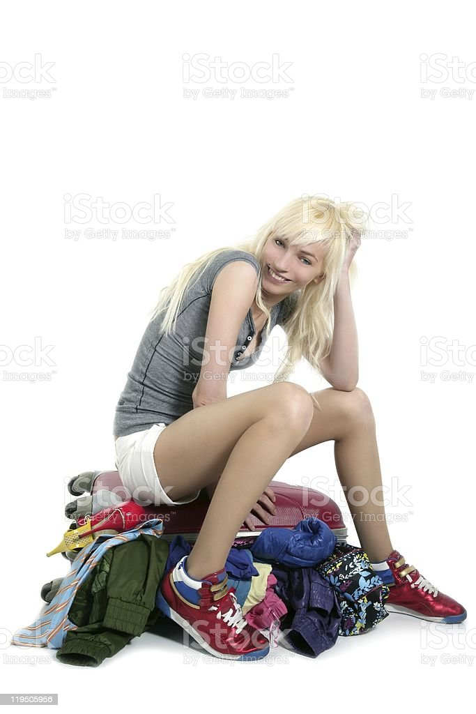 young fashion travel girl closing full clothes suitcase vacation royalty-free stock photo
