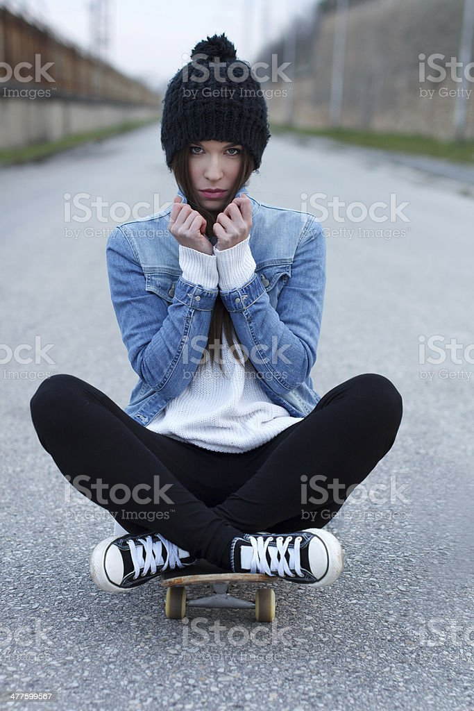 Young fashionable brunette skateboarder girl royalty-free stock photo