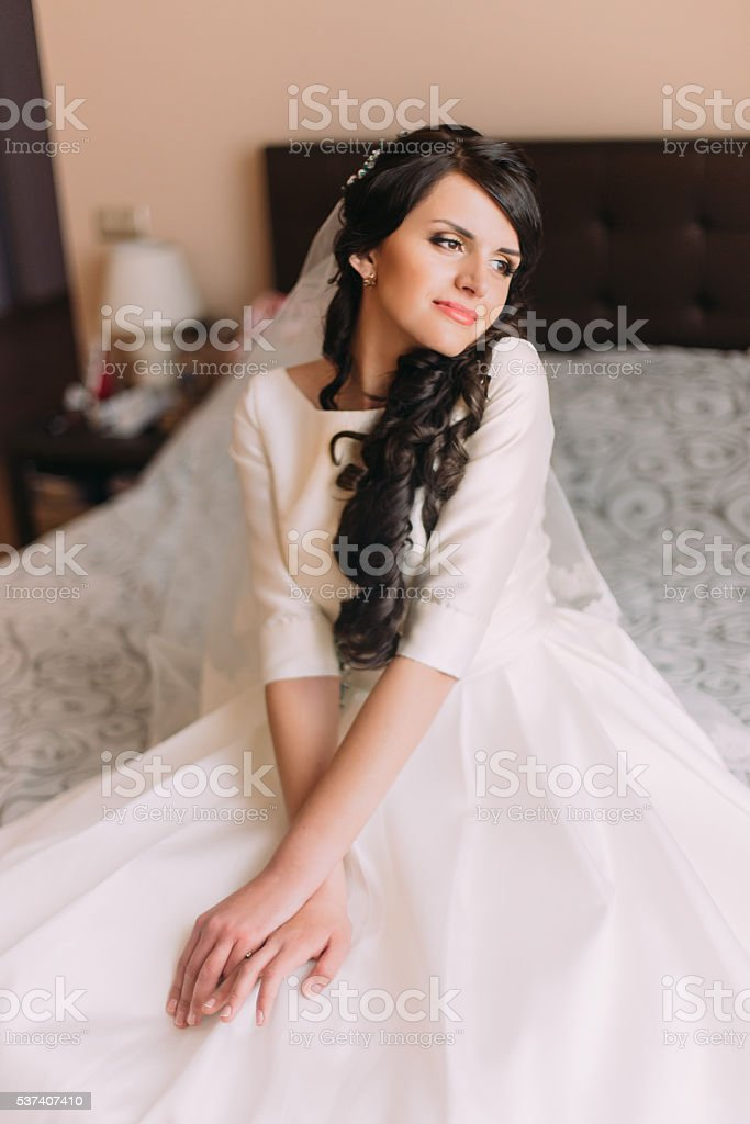 Young fashionable excited bride sitting on bed in wedding dress stock photo