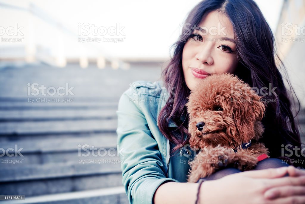 Young fashionable girl holding her toy poodle on the stairs stock photo