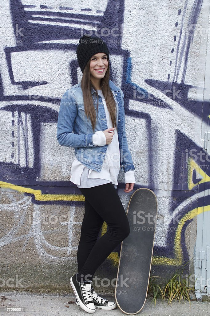 Young fashionable happy brunette skateboarder girl royalty-free stock photo