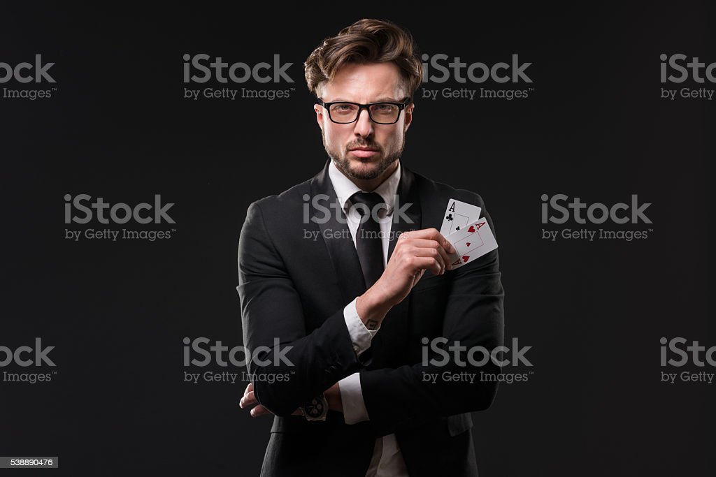 Young fashionable man holding pair of aces stock photo