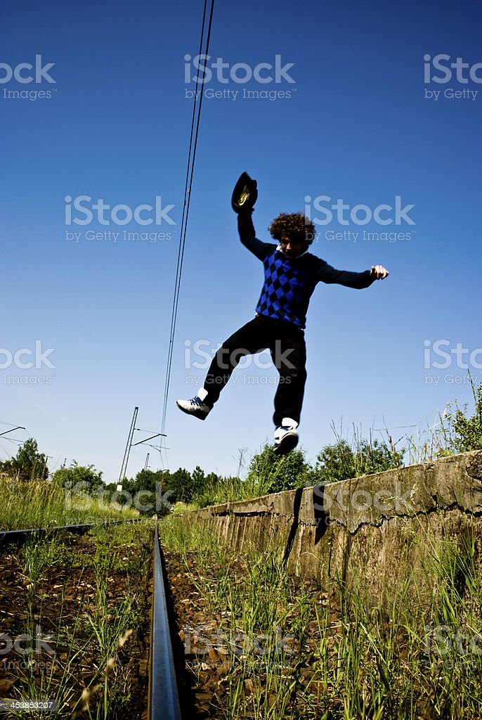 Young fashionable man jumping from train platform on the railway stock photo