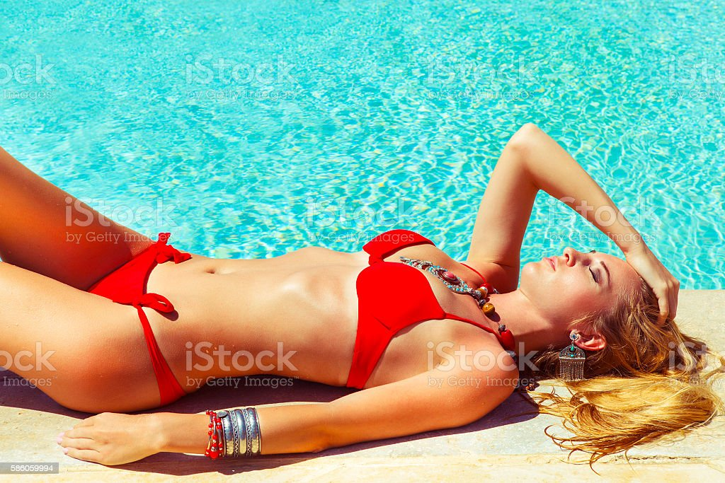 Young fashionable relaxed woman near the pool stock photo