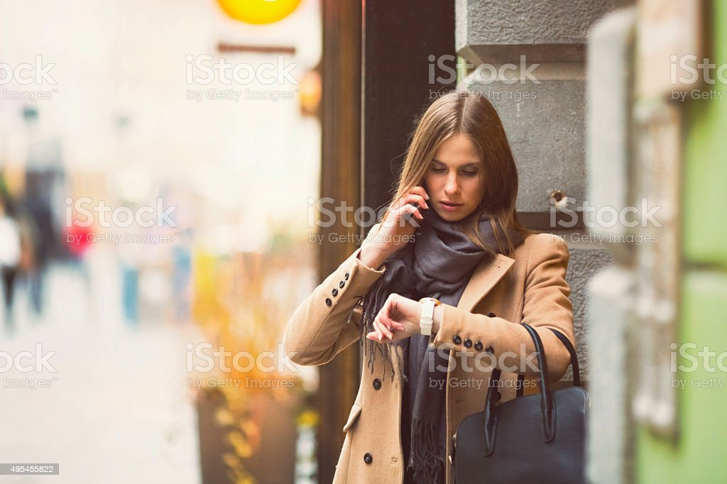 Young fashionable talking on the phone in the street, waiting stock photo
