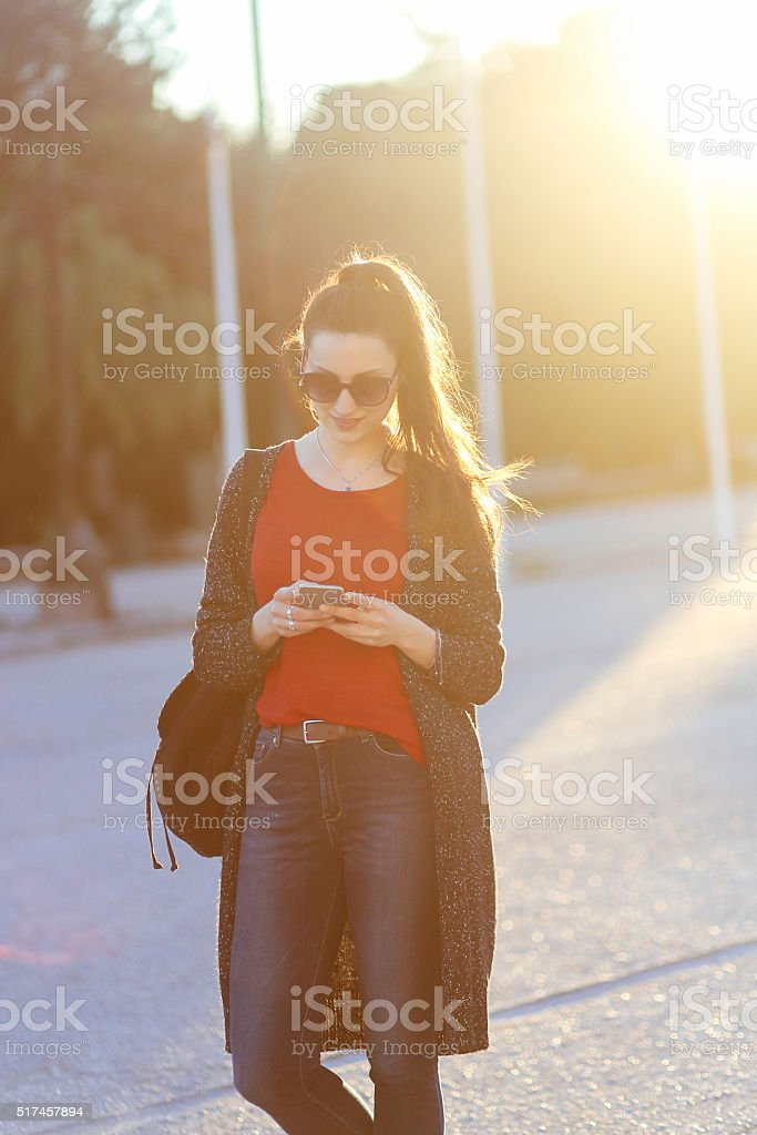 Young fashionable woman checking messages on the phone stock photo