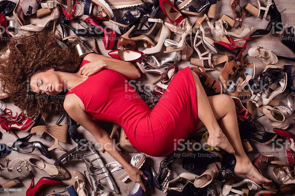 Young fashionable woman lying over stack of shoes stock photo