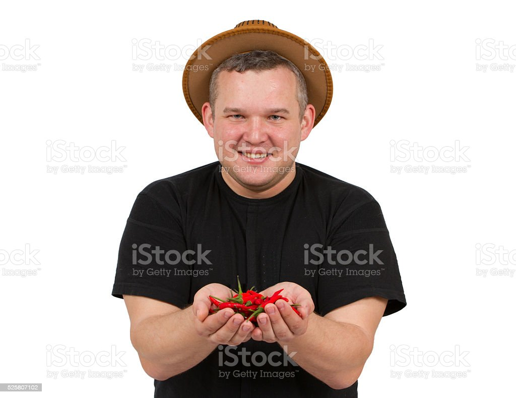 Young fat man with chili in his hands. stock photo