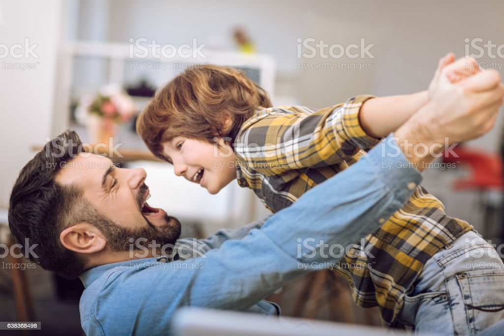 Young father and his son playing indoors stock photo