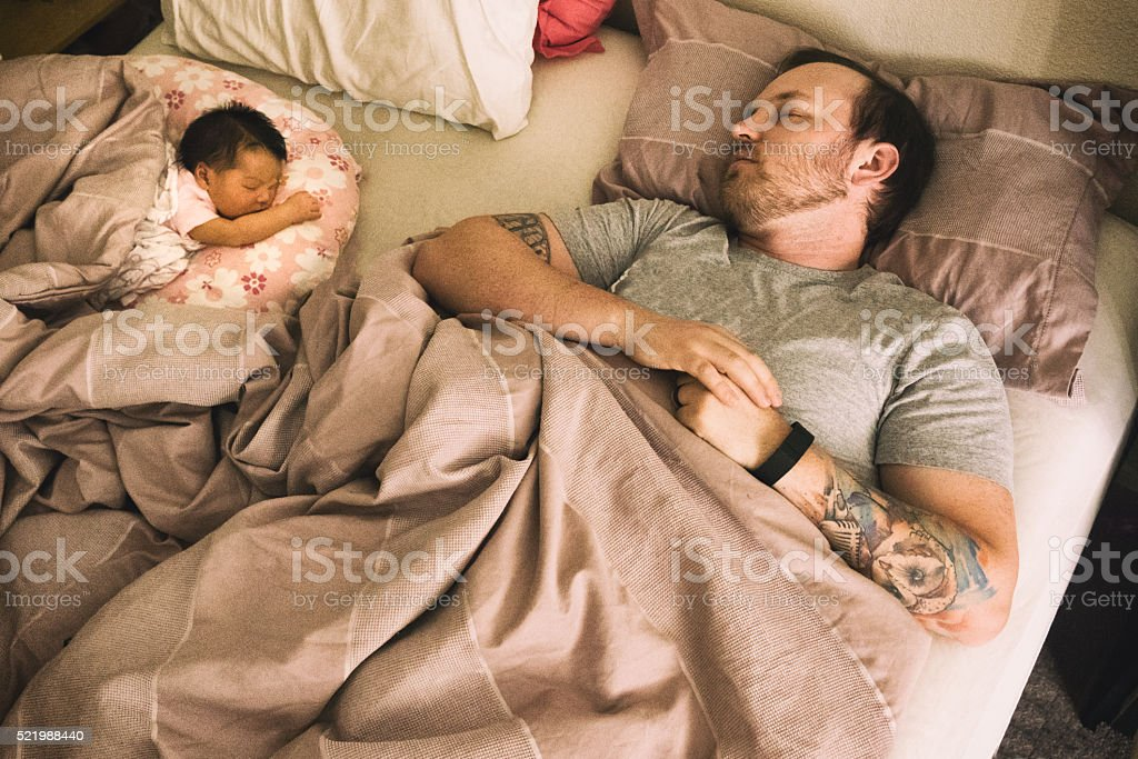 Young Father and Newborn Daughter Sleeping stock photo
