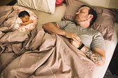 Young Father and Newborn Daughter Sleeping