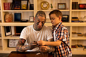 Young father and son adjusting tattoo machine at home.