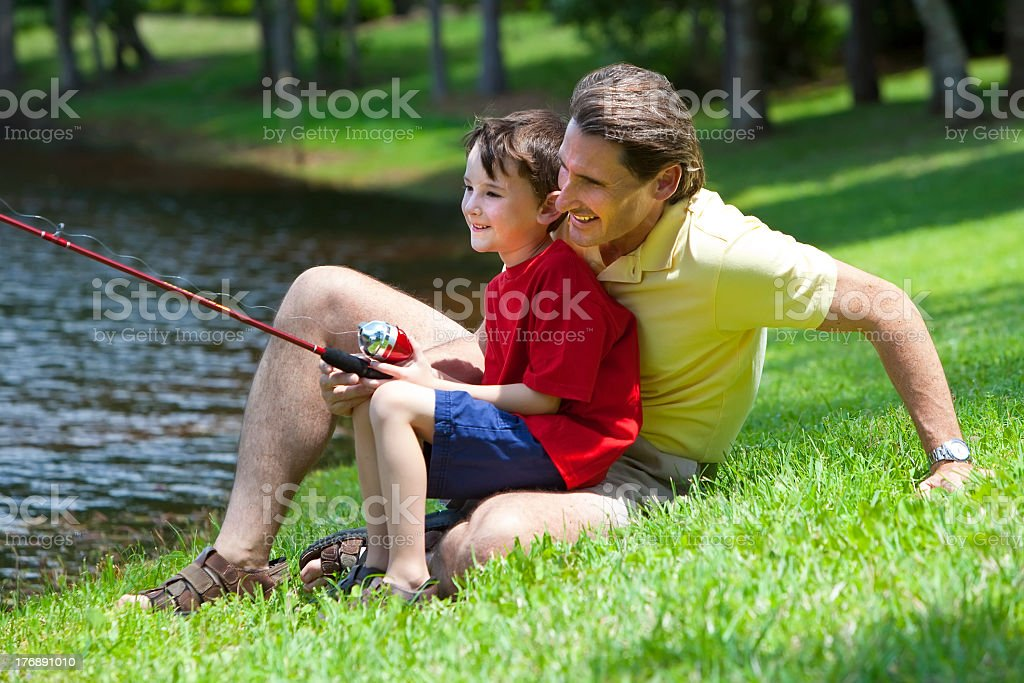 Young father and son fishing from river bank royalty-free stock photo