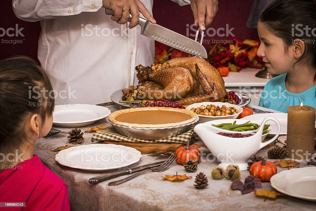 Young father carving thanksgiving turkey for his family royalty-free stock photo