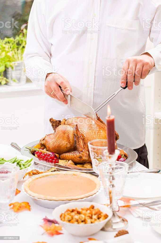 Young father carving thanksgiving turkey for his family stock photo