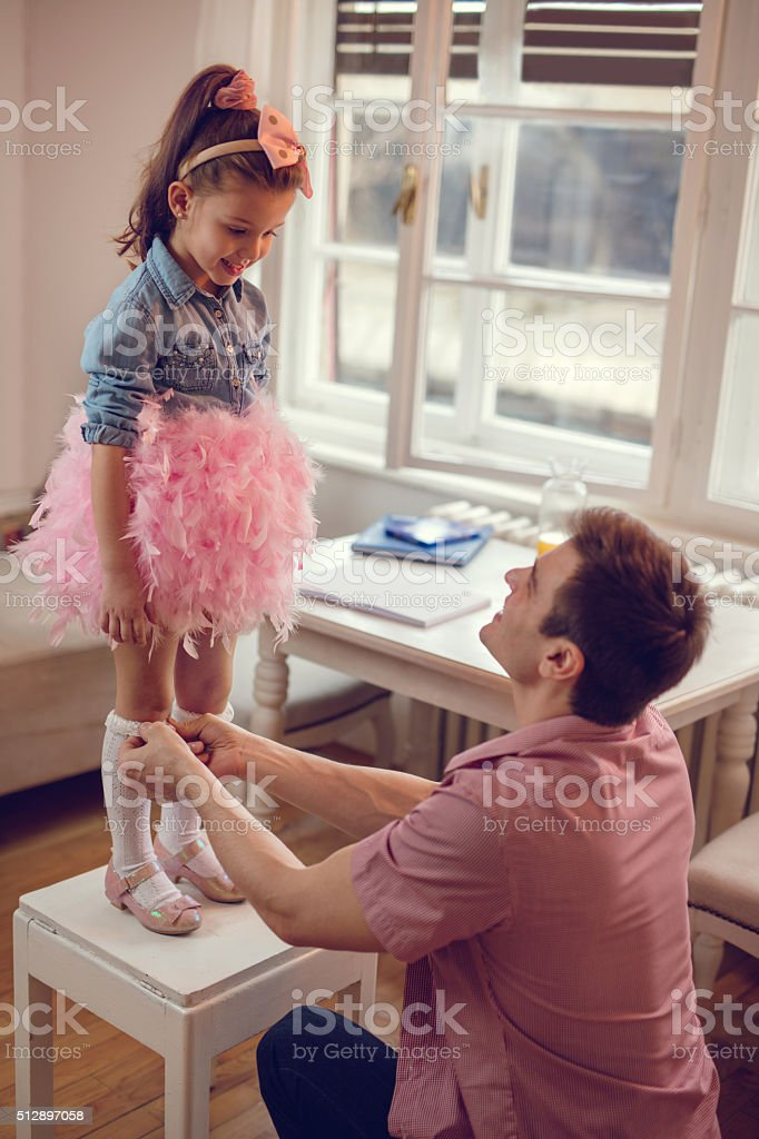 Young father helping his little girl to get dressed. stock photo