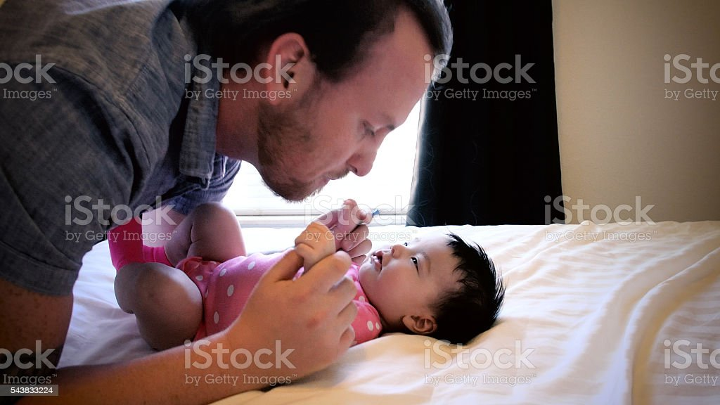 Young Father Playing with Baby Daughter on Bed stock photo