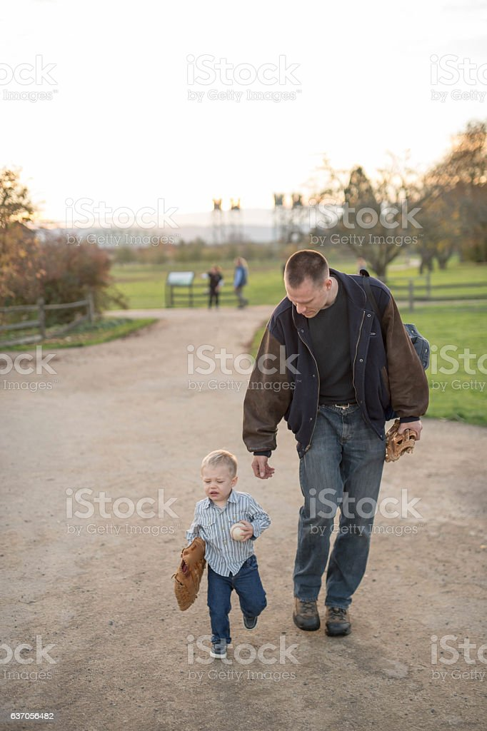Young father playing with his toddler son in a park stock photo