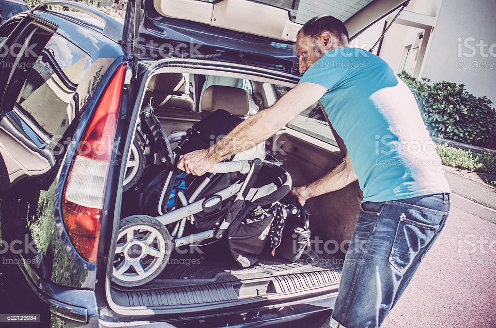 Young father putting baby stroller into the car trunk stock photo