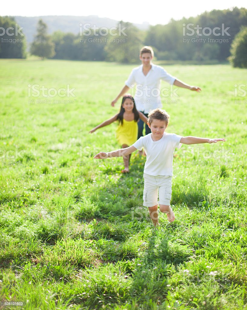 Young father running with kids in meadow stock photo