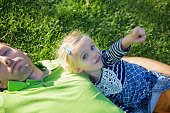 Young father with baby daughter lying on grass