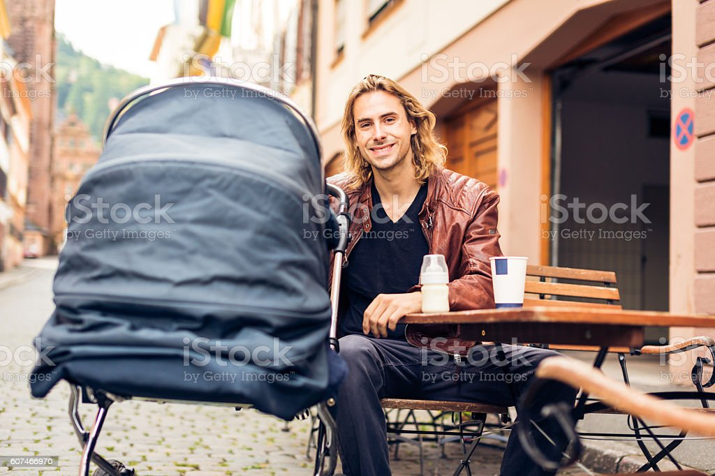 Young father with baby stroller having coffee at a cafe stock photo