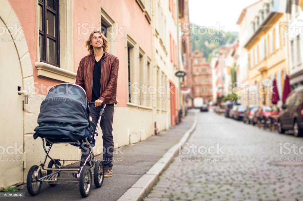 Young father with baby stroller in the city stock photo