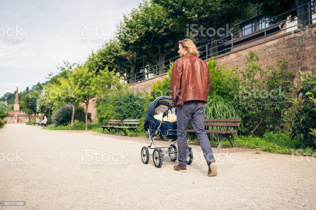 Young father with baby stroller in the park stock photo