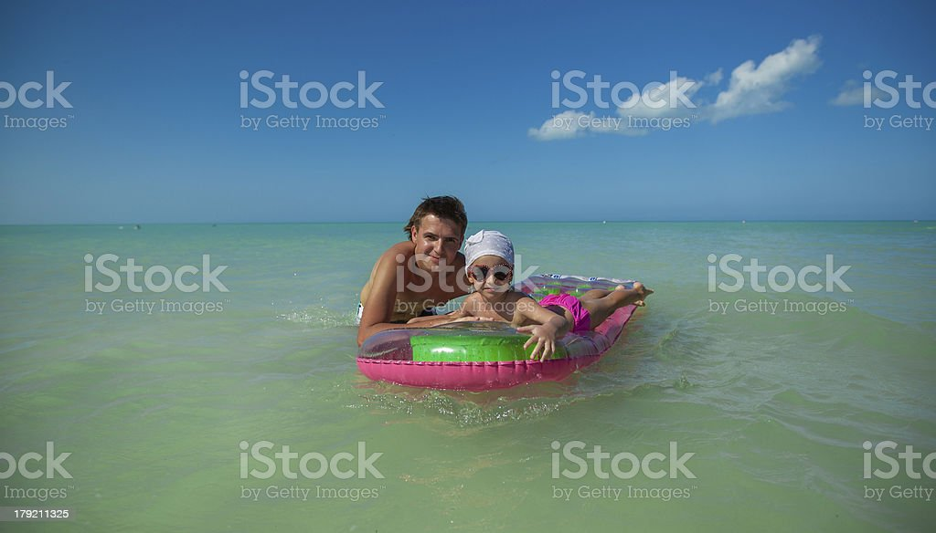 Young father with cute daughter on air mattress in sea royalty-free stock photo